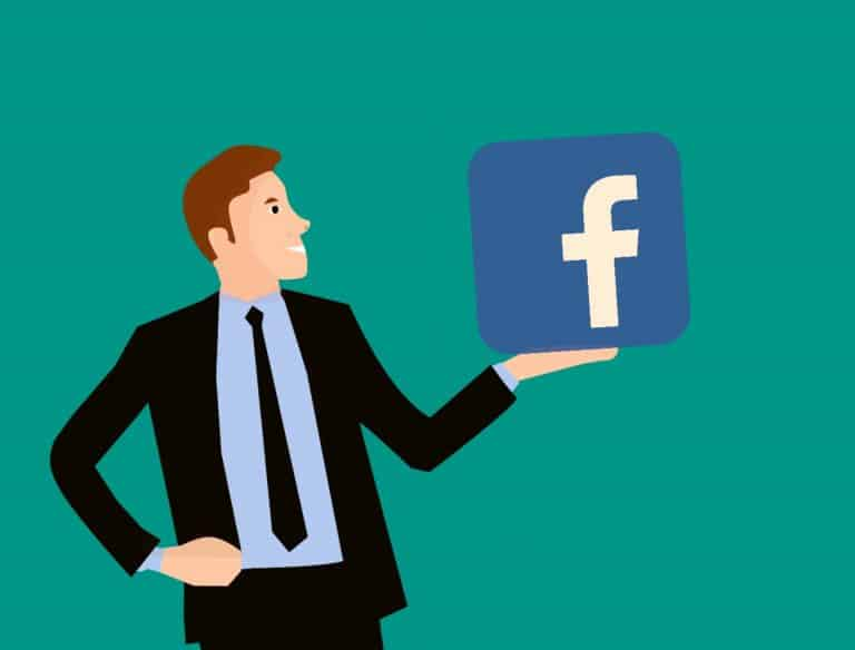 man holding facebook icon in hand