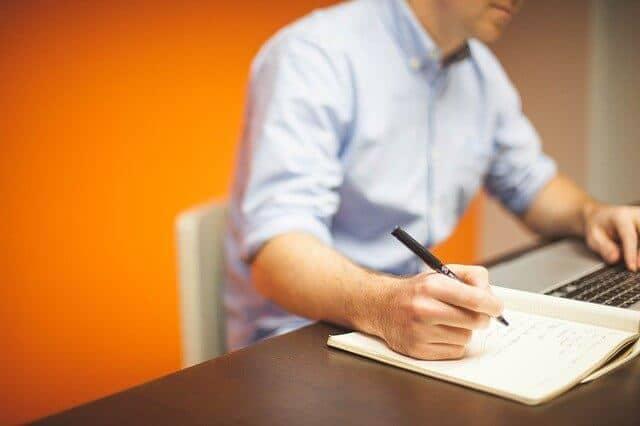 man taking notes sitting at table