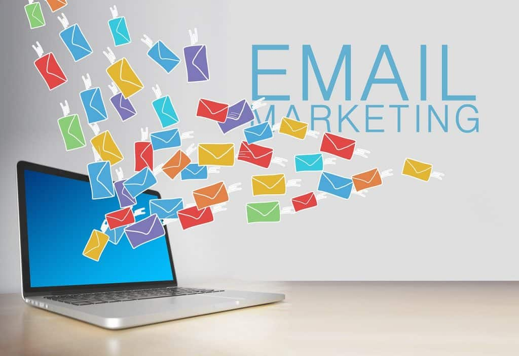 email marketing, laptop on table with email icons